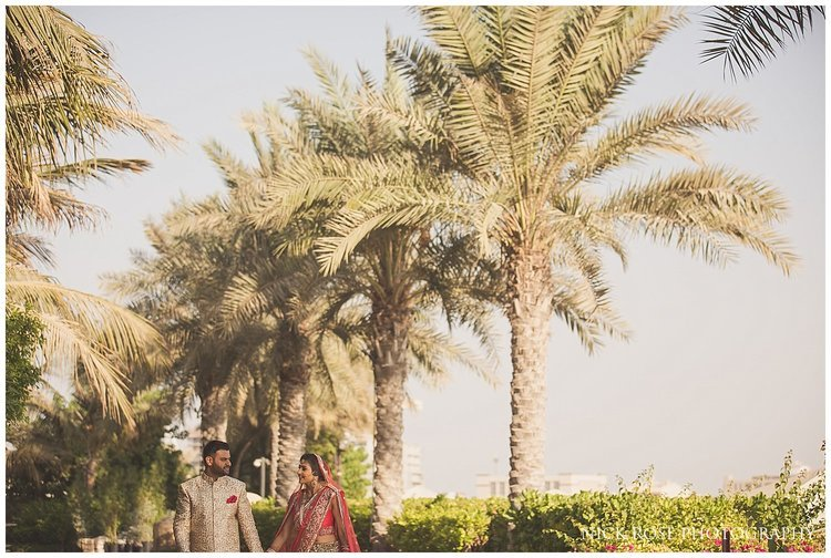 Couple walking under palm trees on the beach in Dubai during a destination wedding