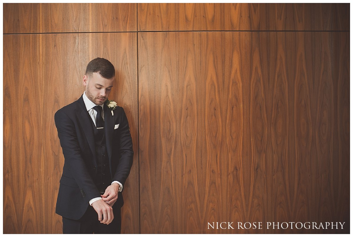 Groom putting on suit getting ready at at Threadneedles Hotel in London