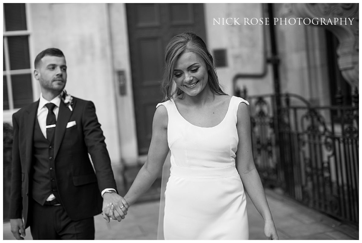 Central London wedding photograph of a bride and groom walking through Guildhall