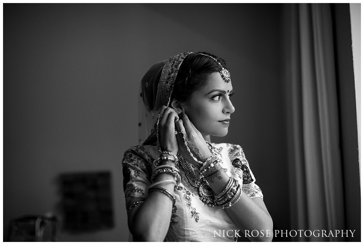 Bride standing by the window at the Grove in Hertfordshire before her hindu wedding