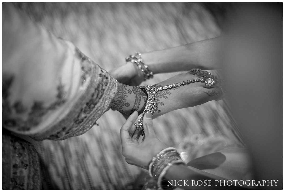 Indian bride having her wedding shoes put on by bridesmaid before a wedding at the Grove