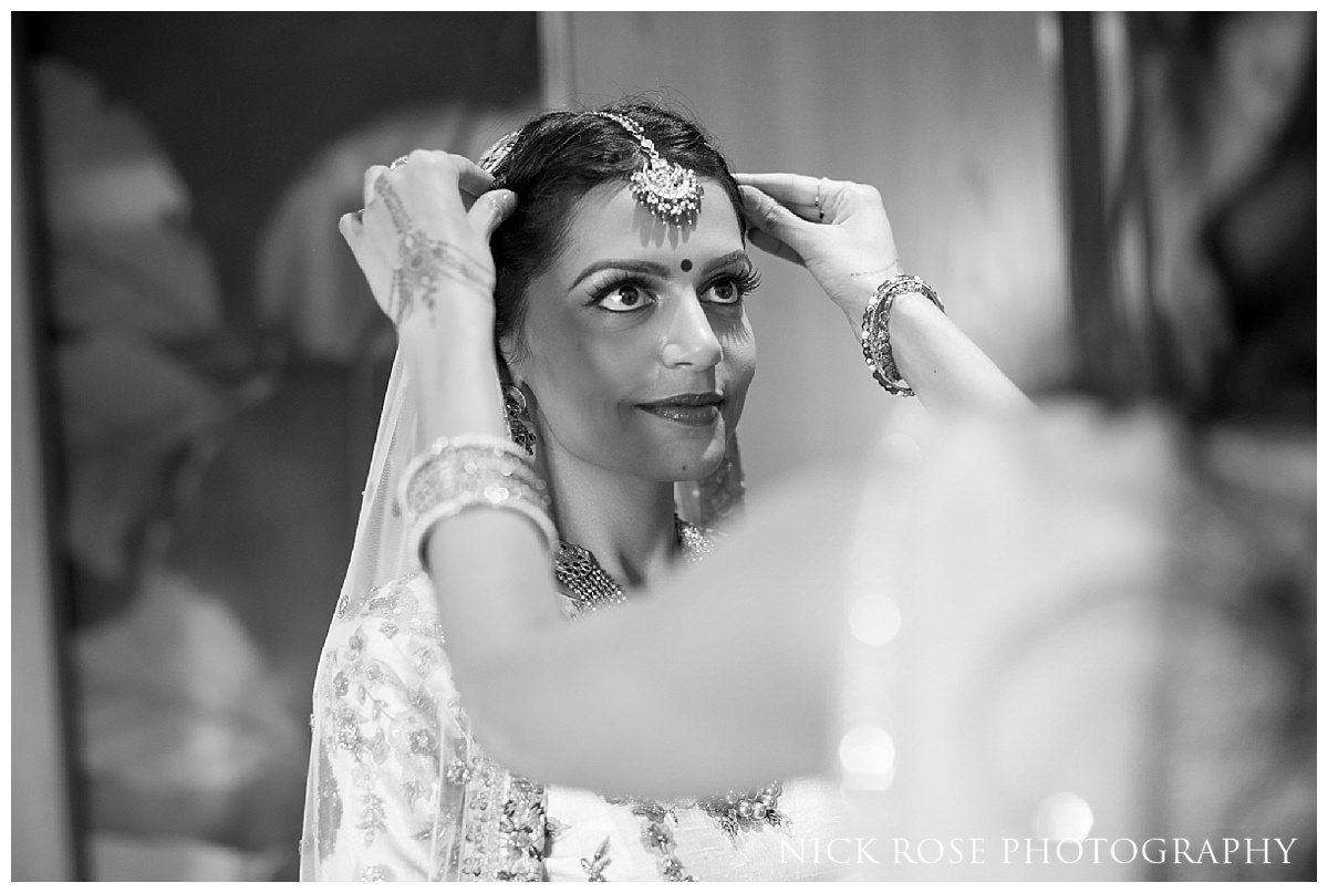 Asian bride having the final touches to her makeup put on at The Grove in Chandler's Cross