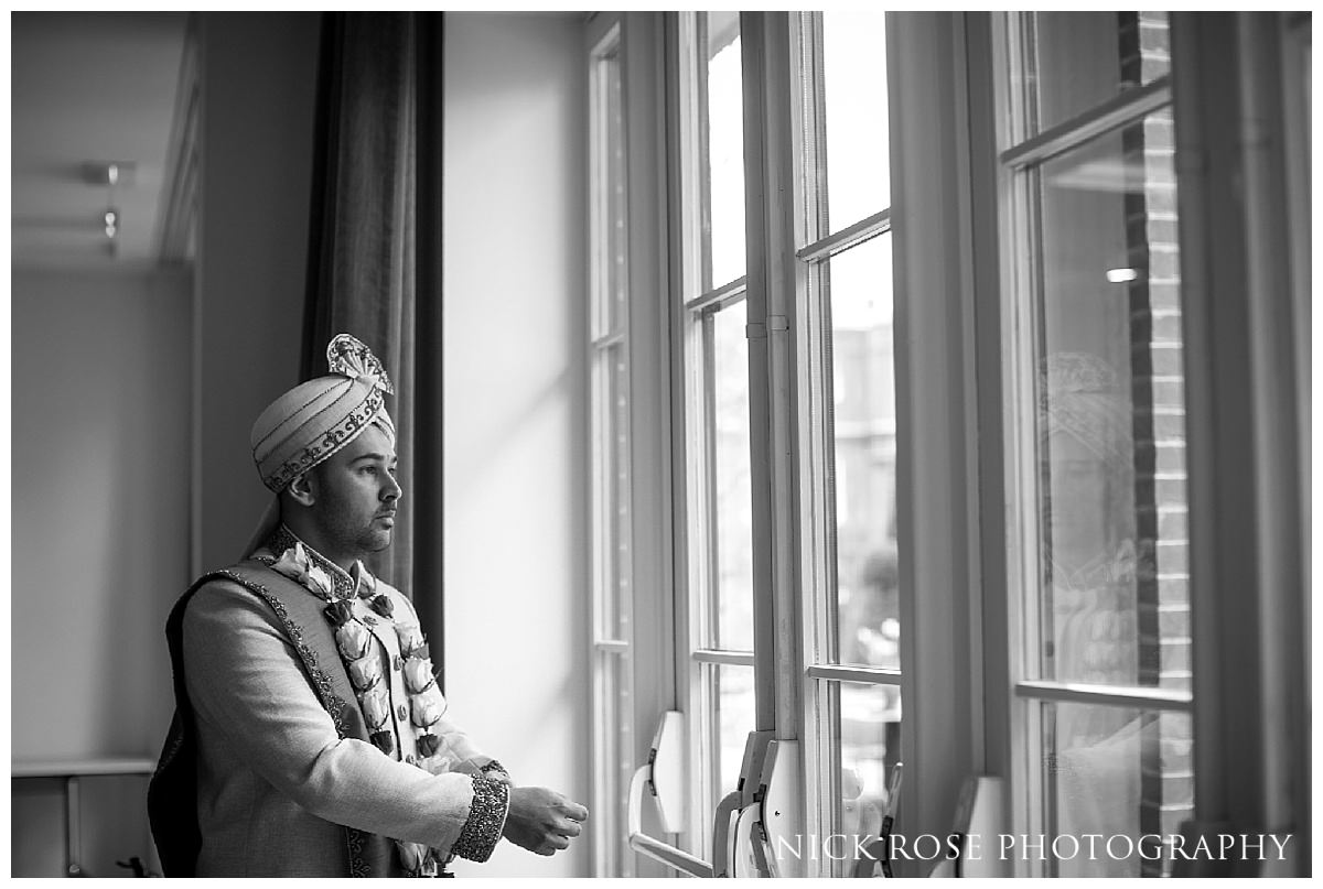 Indian groom standing by the window before his Asian wedding ceremony in Hertfordshire