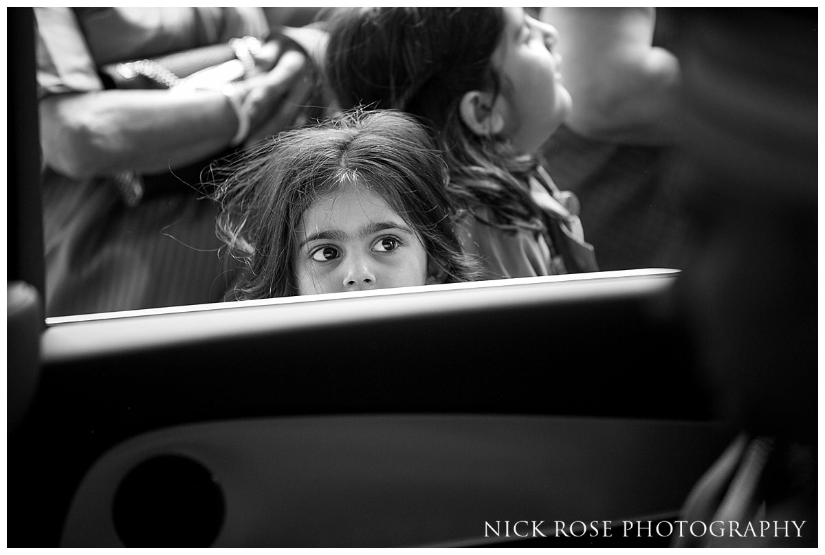 Little girl looking through a car window at the groom before his Hindu wedding