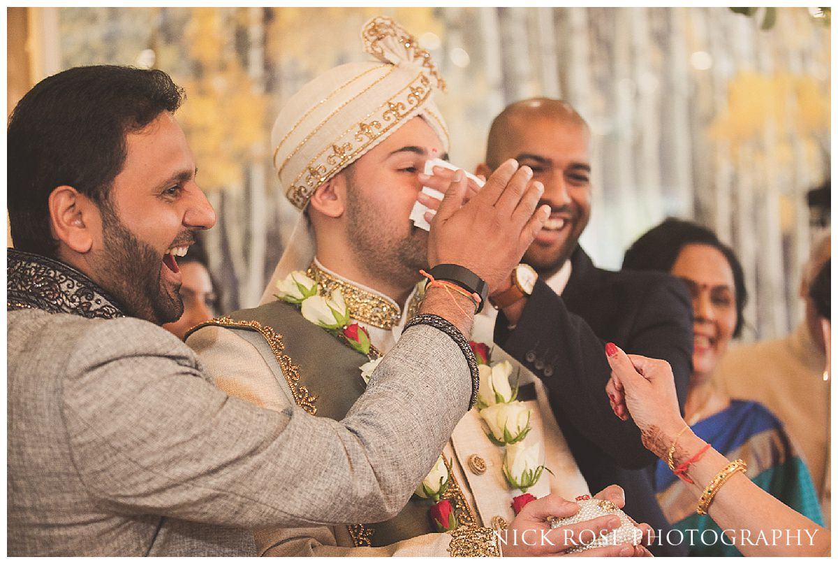 Groom having his nose rubbed by the bride's mother during a Hindu wedding ceremony in Hertforshire