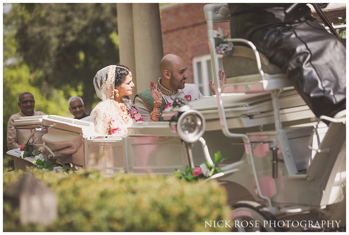 Bride and groom exiting a Hindu wedding at The Grove in Hertfordshire on a horse and carriage