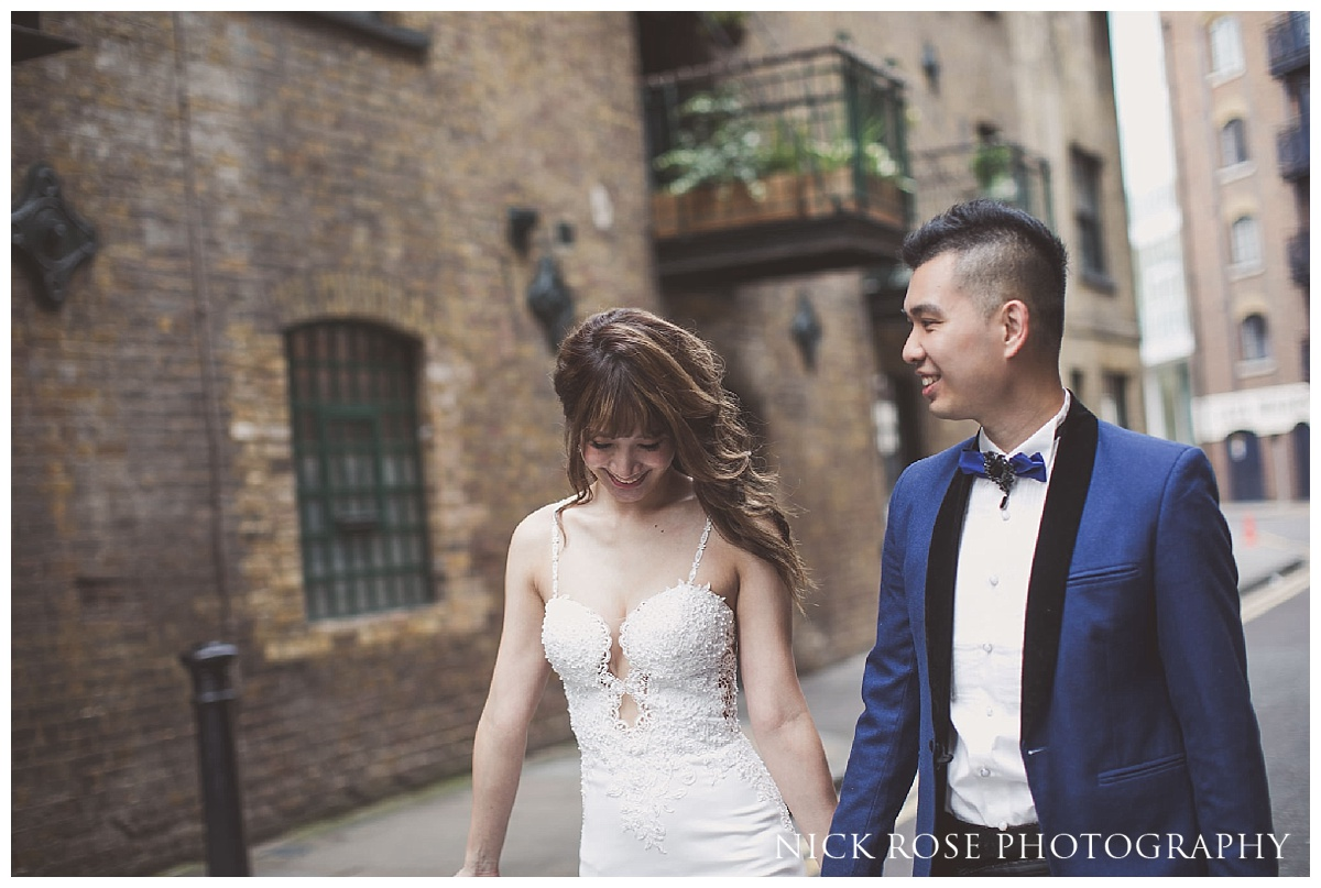 Couple walking along Shad Thames and holding hands for their Shad Thames pre wedding photo shoot in London