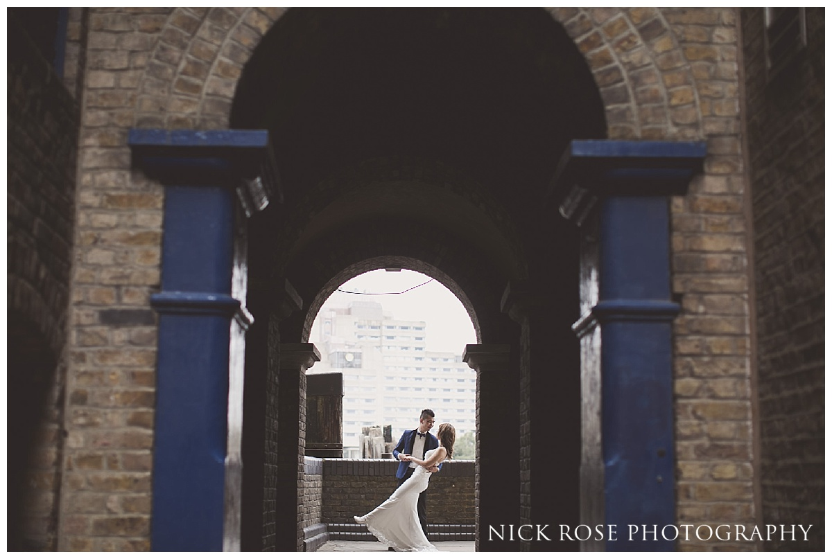 Groom dancing with bride for a pre wedding shoot along the River Thames in London