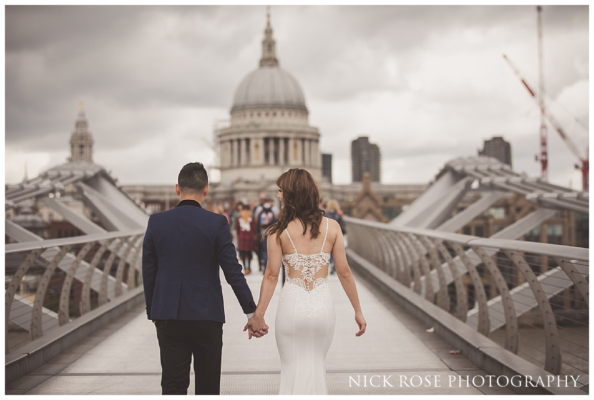 Couple walking over Millennium Bridge and golding hands for a pre wedding shoot in front of St Pauls Cathedral on London