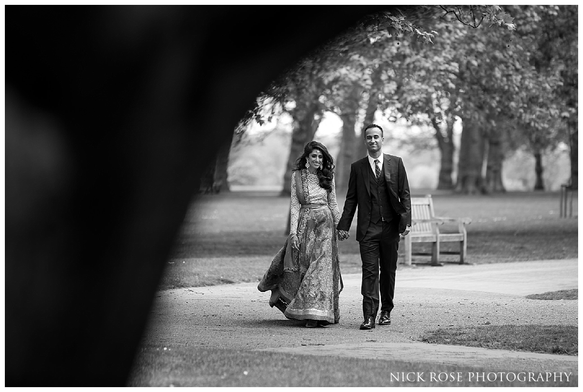 South Asian bride and groom walking through Hyde Park in London for a pre wedding photography portrait