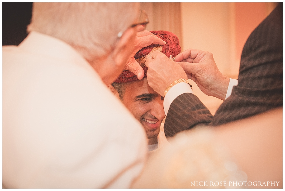 Pakistani groom having his turban tied before a South Asian wedding at the London Ritz Hotel in Piccadilly