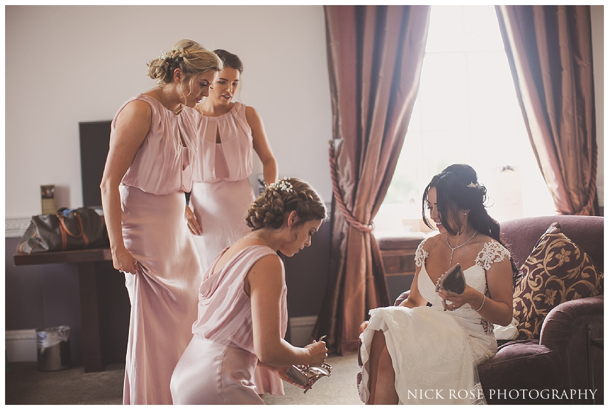 Bridesmaids helping bride get ready for a Buxted Park hotel wedding in East Sussex