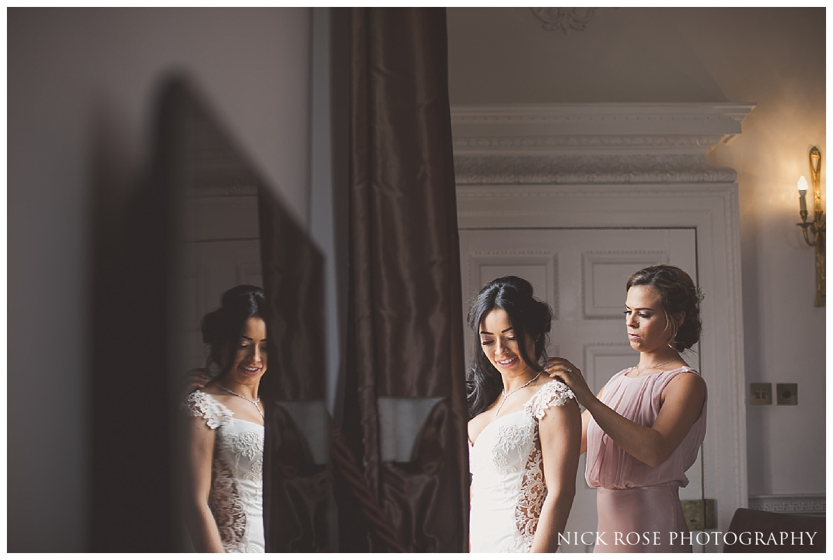 Bride putting on dress for a Buxted Park hotel wedding in East Sussex