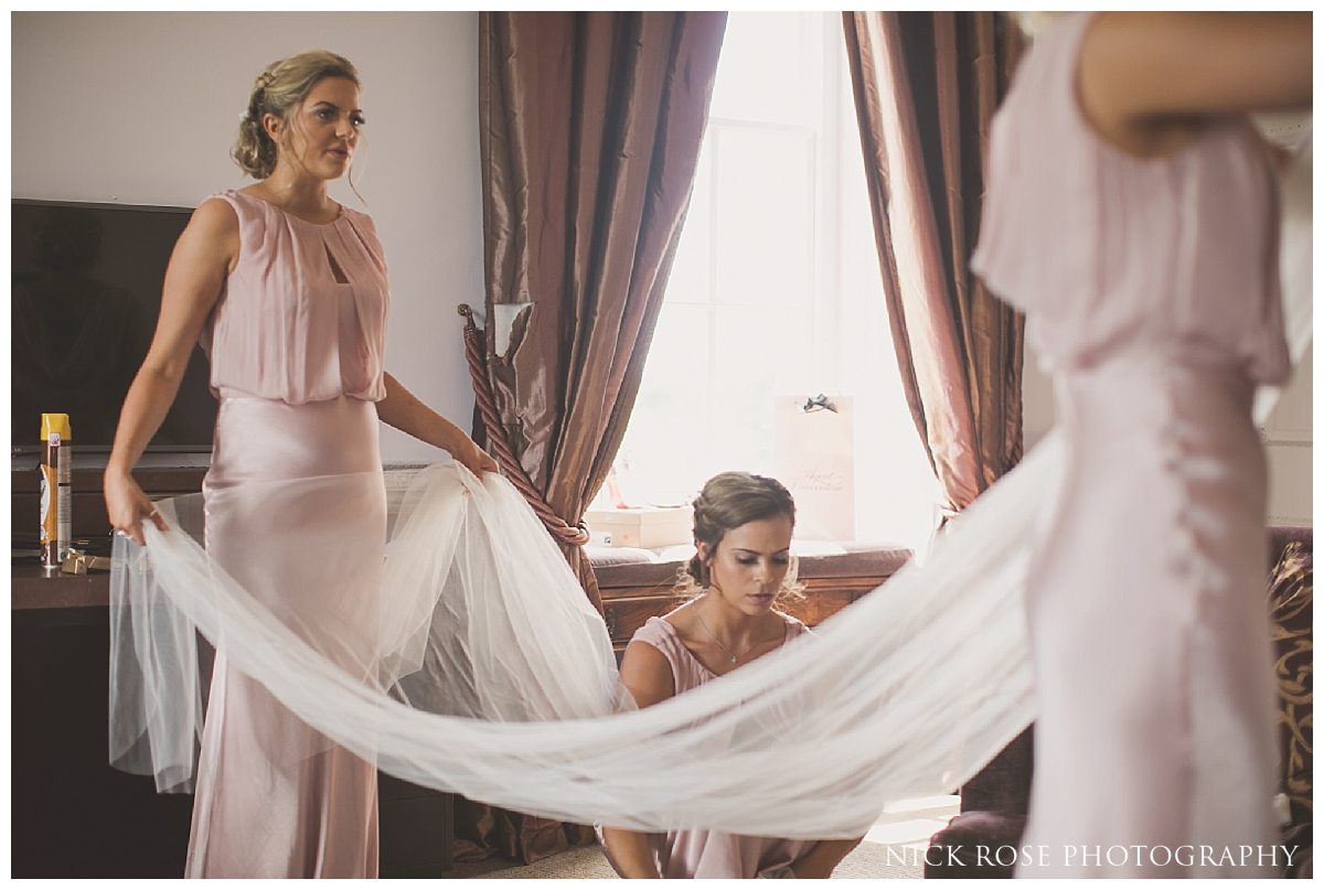Bridesmaids putting on brides veil before her Buxted Park hotel wedding in East Sussex