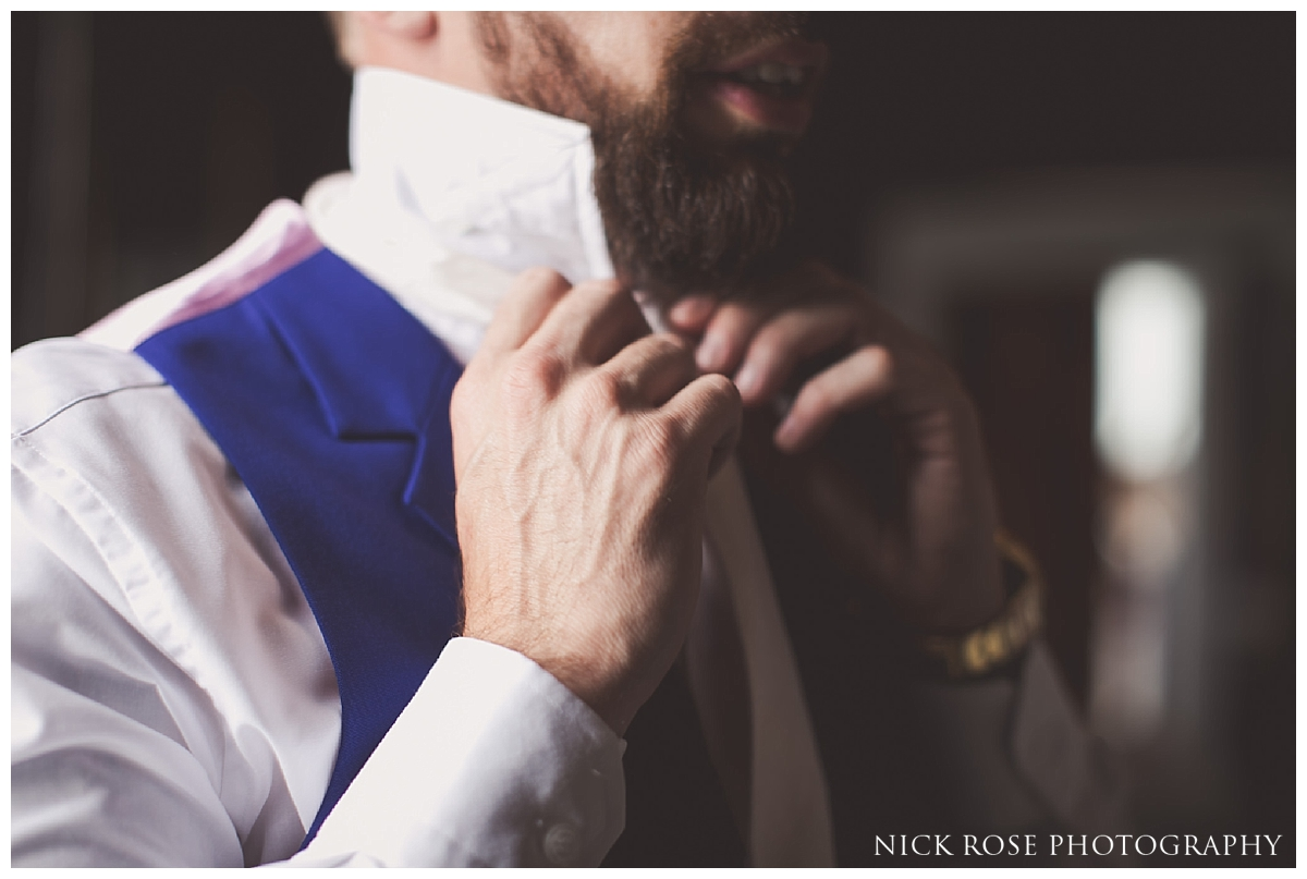 Groom putting on tie before a Buxted Park hotel wedding in East Sussex