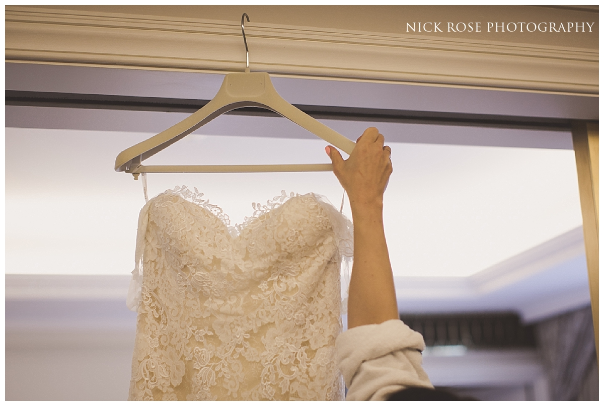 Bride reaching for her dress before a Mayfair wedding in London