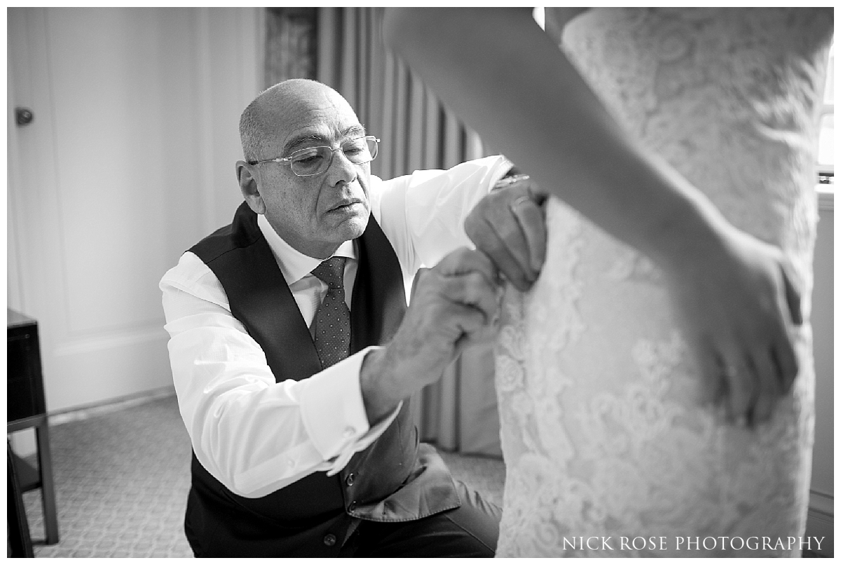 Brides father helping to put on daughters wedding dress for a central London wedding at Dartmouth House in Mayfair