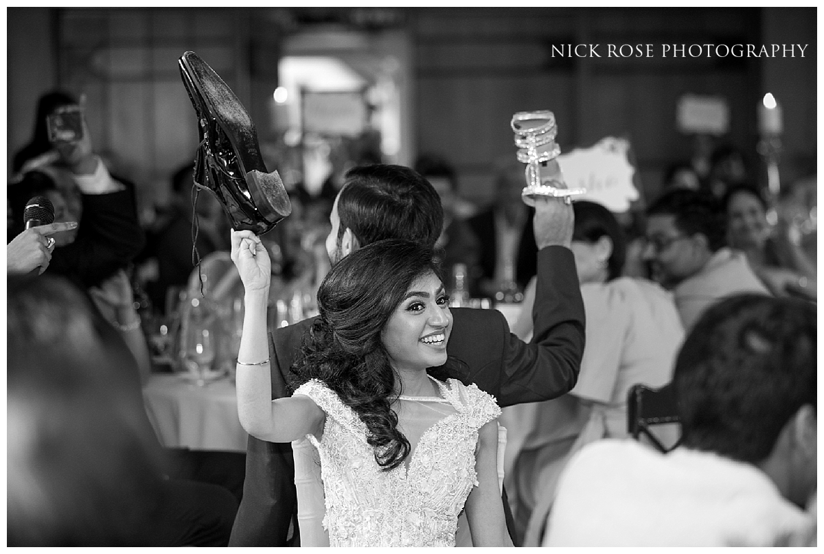 Bride and Groom playing the fun shoe game during a Sikh civil wedding reception in Buckinghamshire