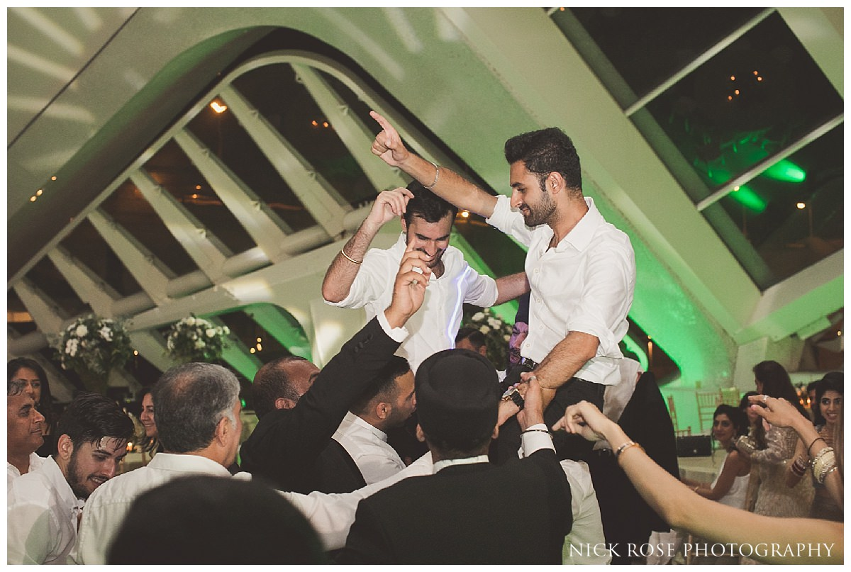 Ushers dancing on shoulders during a Sikh wedding in Valencia Spain