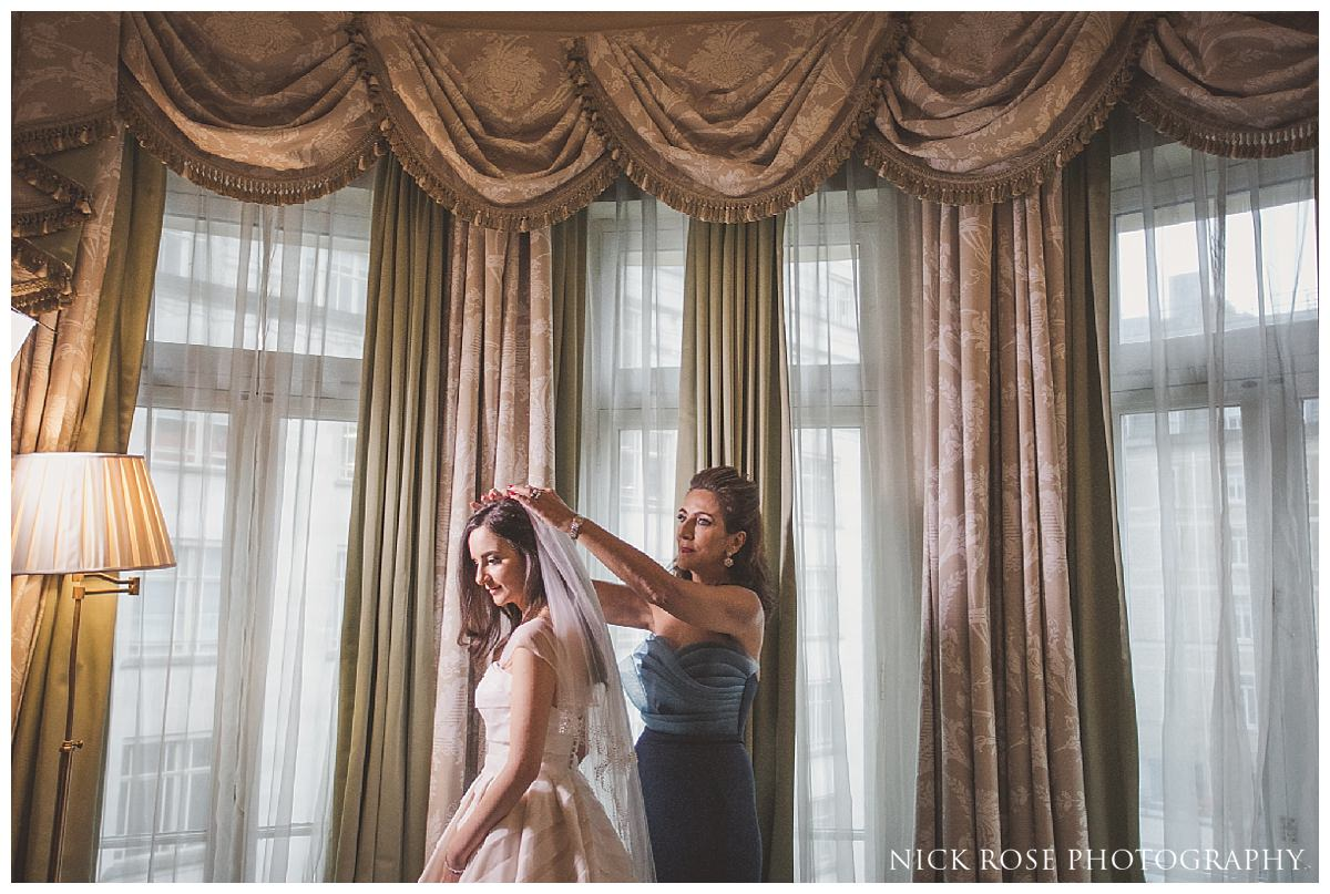 Brides mother helping her daughter get ready for a Savoy London wedding