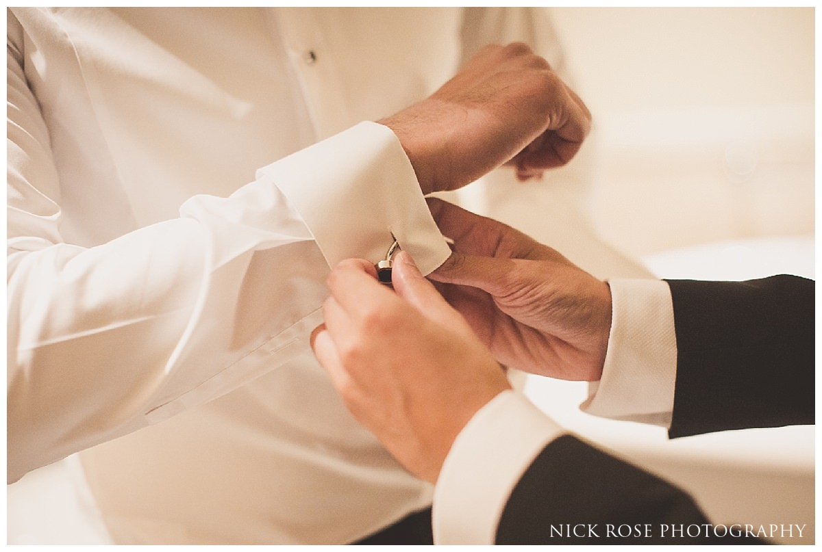 Groom putting cufflinks on before a Savoy London wedding