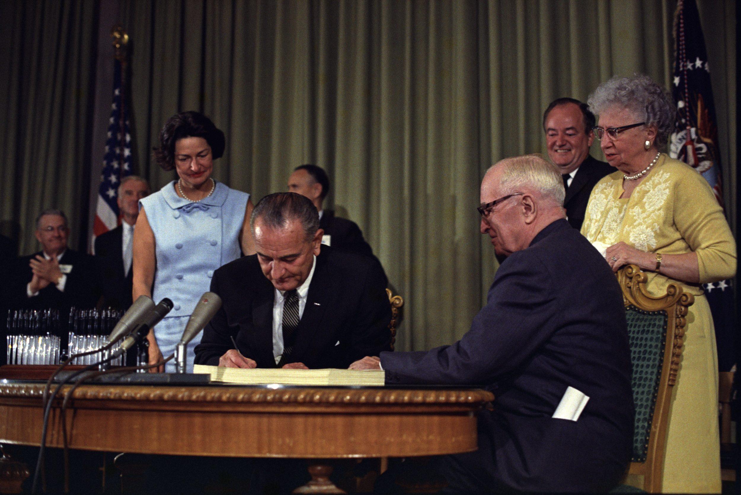 Lyndon_Johnson_signing_Medicare_bill,_with_Harry_Truman,_July_30,_1965.jpg