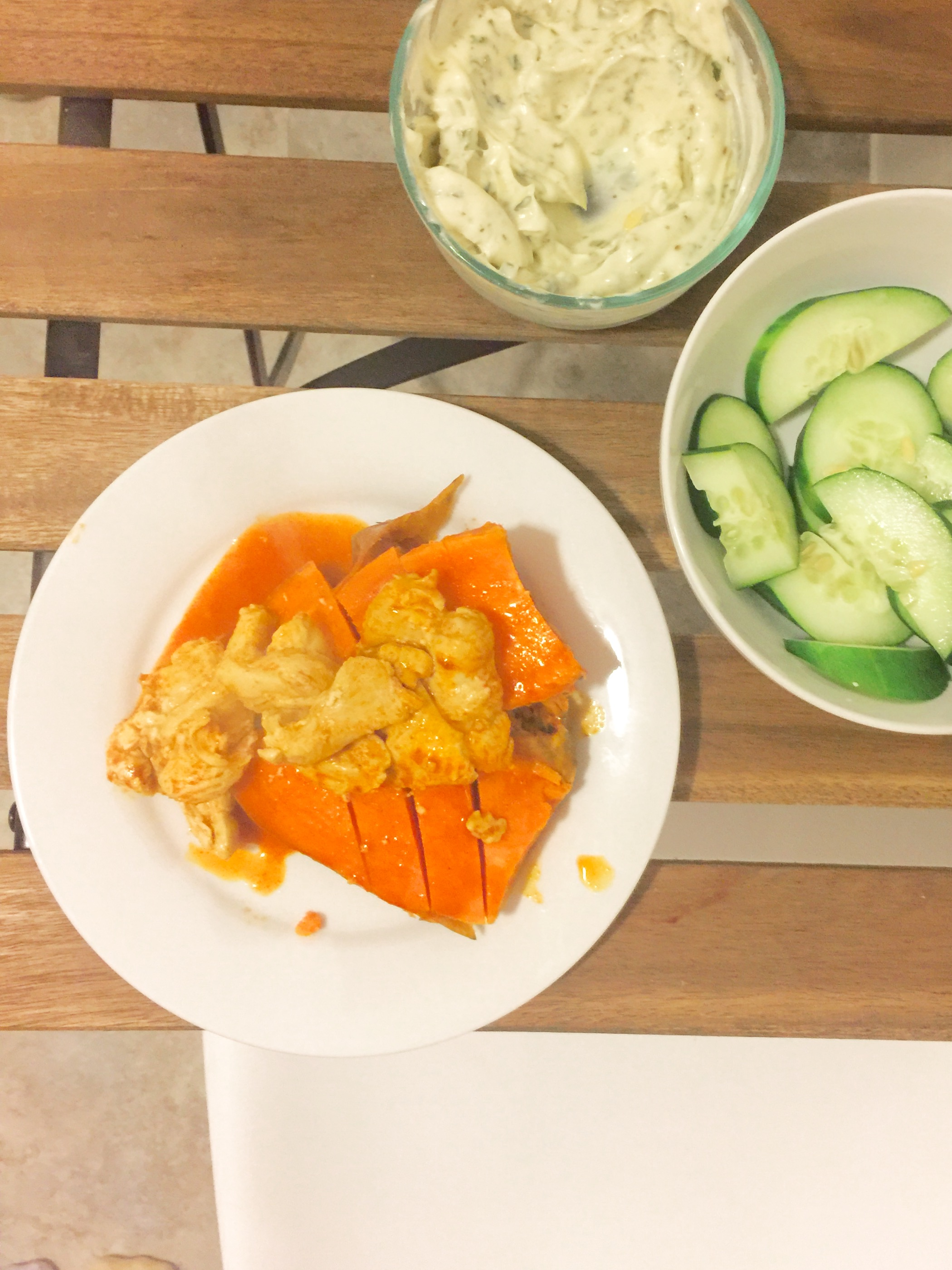 Buffalo chicken on a sweet potato with cucumbers and ranch