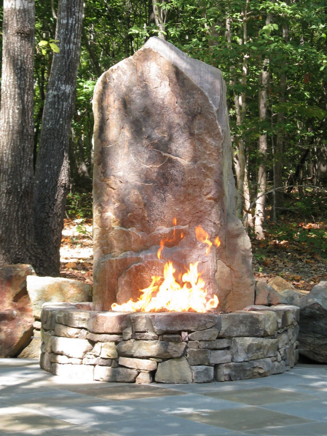 A vertical boulder stands as a dramatic focal point for this fire pit and sitting area.