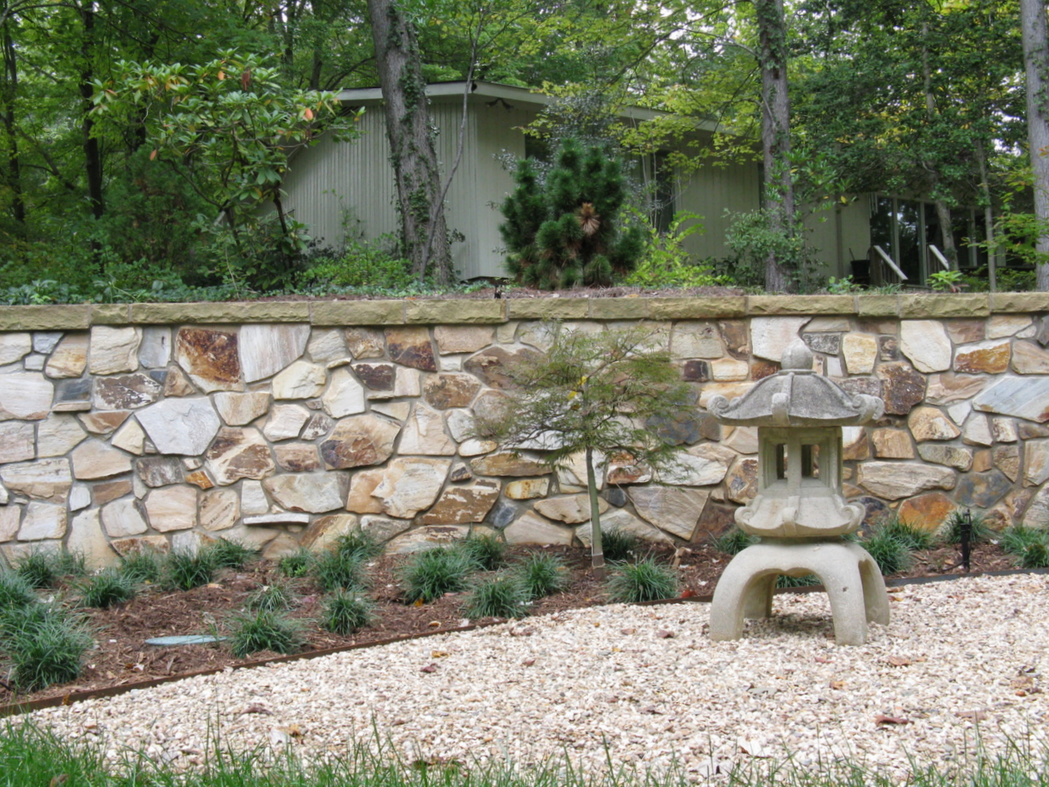 Retaining wall with sandstone cap and rock garden in foreground