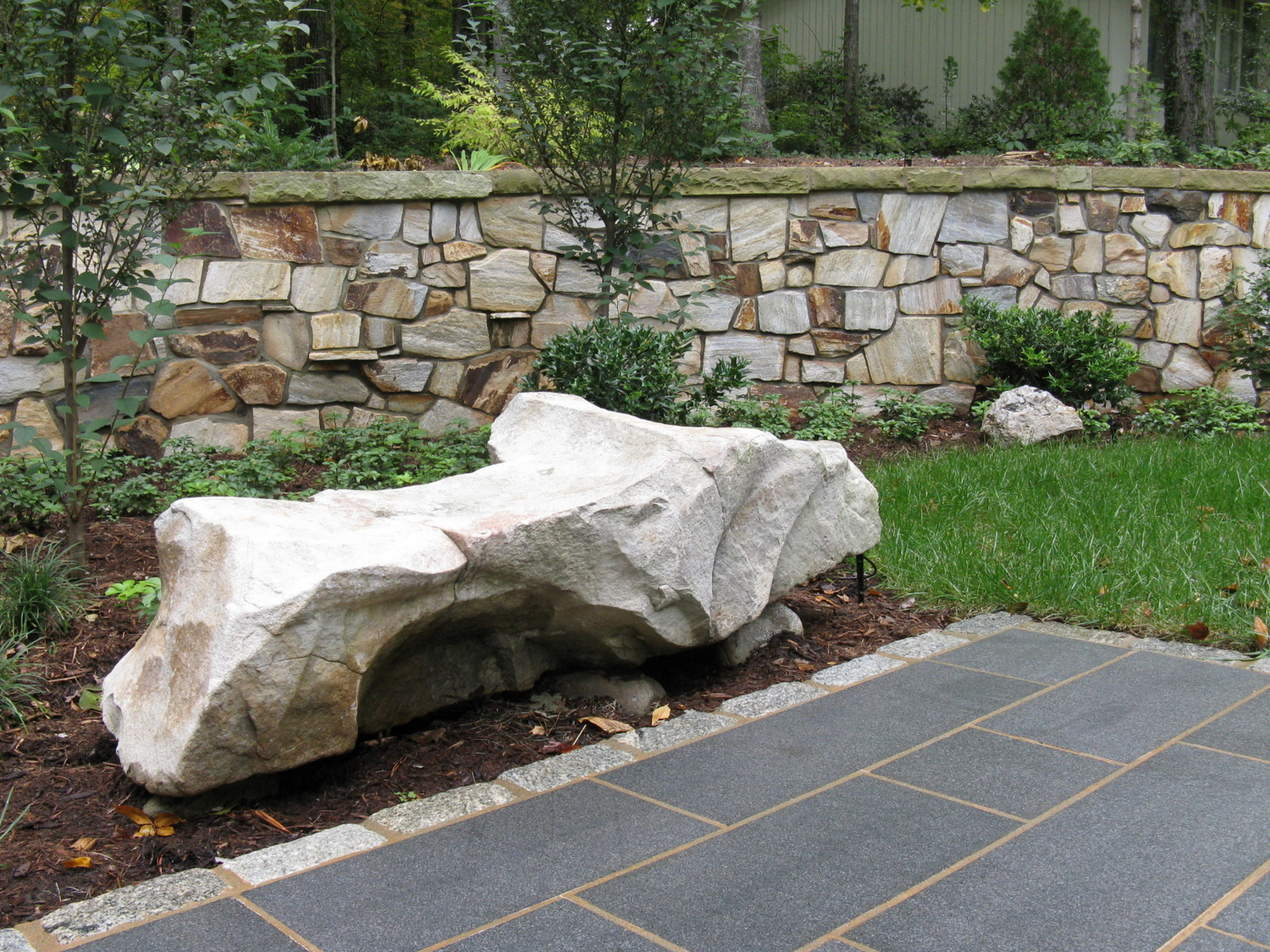 A sculptural sandstone bench accents the walkway.