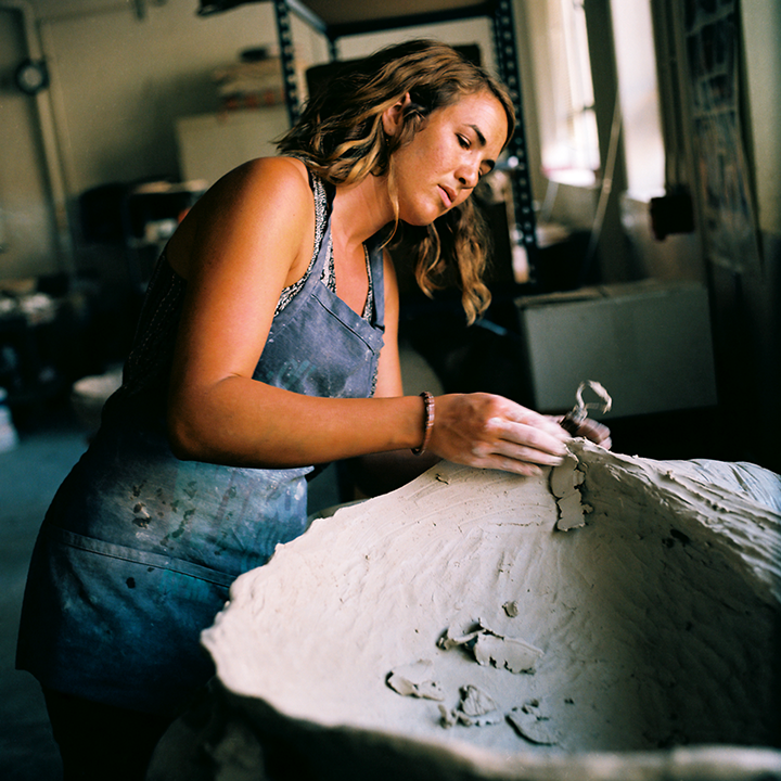 Malia Landis at work with a commission piece for an abalone shell sink.  Photo © Aimee Santos