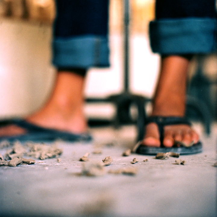 Clay shavings on the floor are a common element in Landis' life and being from Hawaii sandals are too. Photo © Aimee Santos