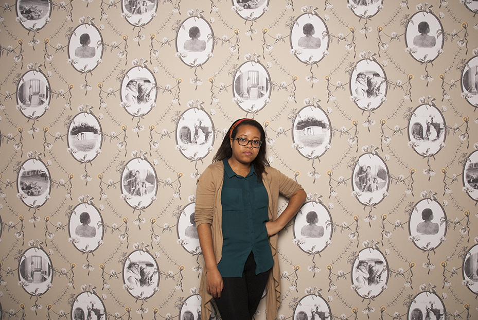 Carla Jay Harris, a graduate student at UCLA, stands in front of her wall paper created through reapropriated imagery and self portraiture.  Photo © Aimee Santos