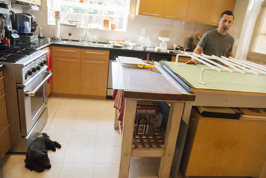Inside Tomczyk's home studio is in his kitchen with his two year old Yorkie/Poodle mix named Rico by his side.  Photo © Aimee Santos