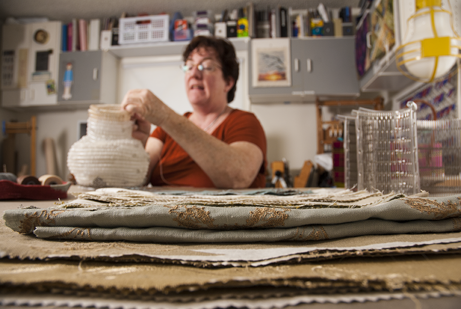 Julie Kornblum creates a sculpture utilizing her basket weaving skills in her studio in Woodland Hills surrounded by fabric, found objects and non-traditional textile materials.  Photo © Aimee Santos