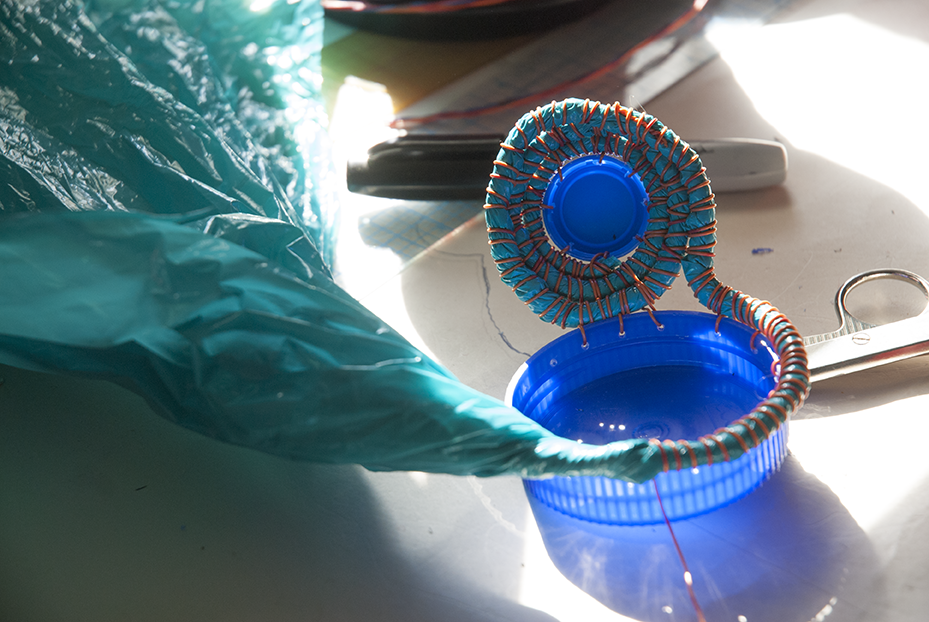 A piece in it's inception involves bottle caps, plastic bags and wire as well as time punching holes into the larger pieces to allow for a smooth transition in the weaving process. Photo © Aimee Santos