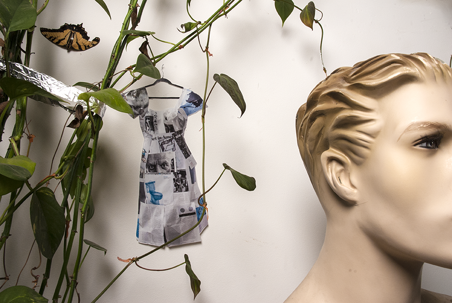 A miniature detail of Szabo's magazine dress hangs on the wall behind one of many plants and next to a male mannequin bust.  Photo © Aimee Santos