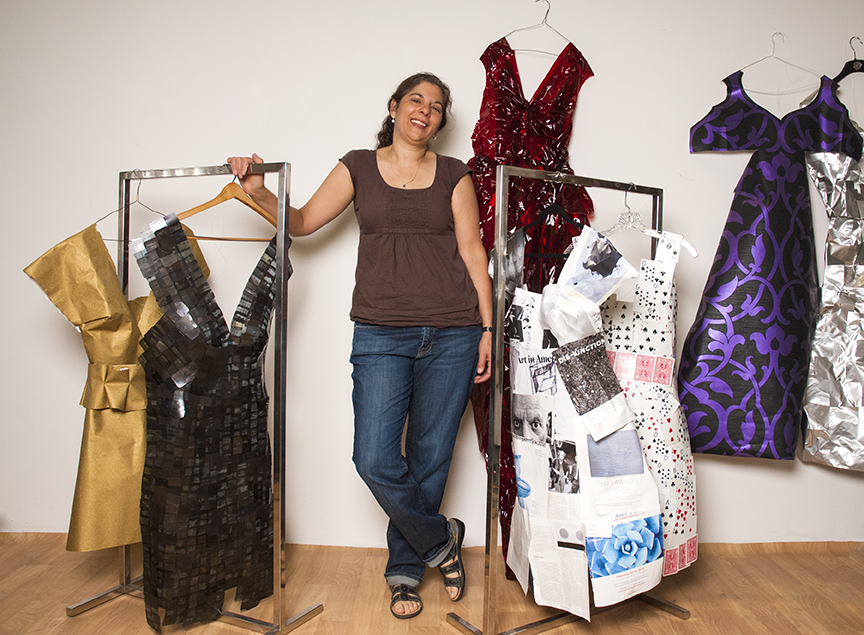 Los Angeles based photographer, Jane Szabo, poses with a variety of dresses she has created for her project 'Reconstructing Self.'  (L-R) Gold Lame/Wallpaper dress, Dental Films dress, Red Cellophane dress, Art In America Magazine dress, Deck of Cards dress, Wallpaper dress, Aluminum Foil dress.  Photo © Aimee Santos