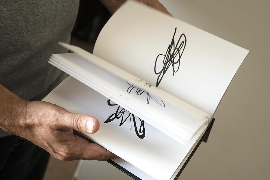 Tm Gratkowski flips through one of his many sketch books. Photo © Aimee Santos
