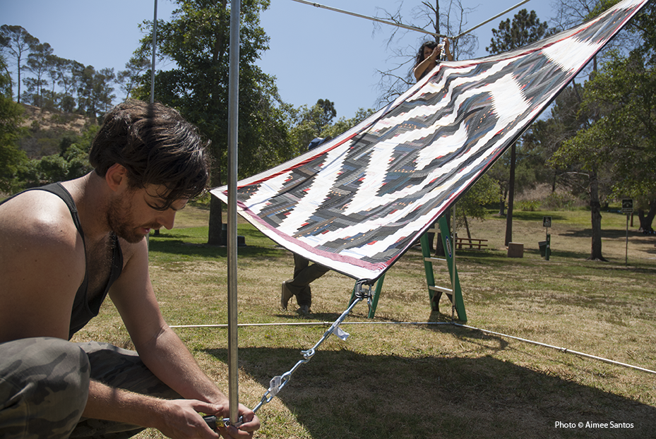 Luke Haynes tests a theory of presentation with one of his 'Log Cabins of Donald Judd' quilts in Elysian Park in Los Angeles, CA. Photo © Aimee Santos
