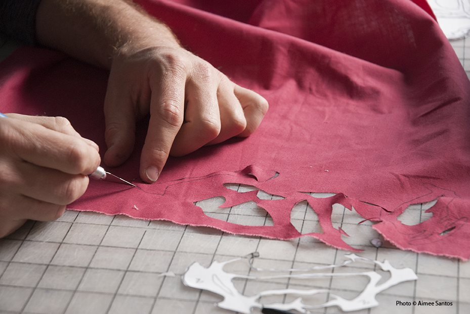 Haynes cuts intricately cut pieces of cloth to complete a commission for a client. Photo © Aimee Santos