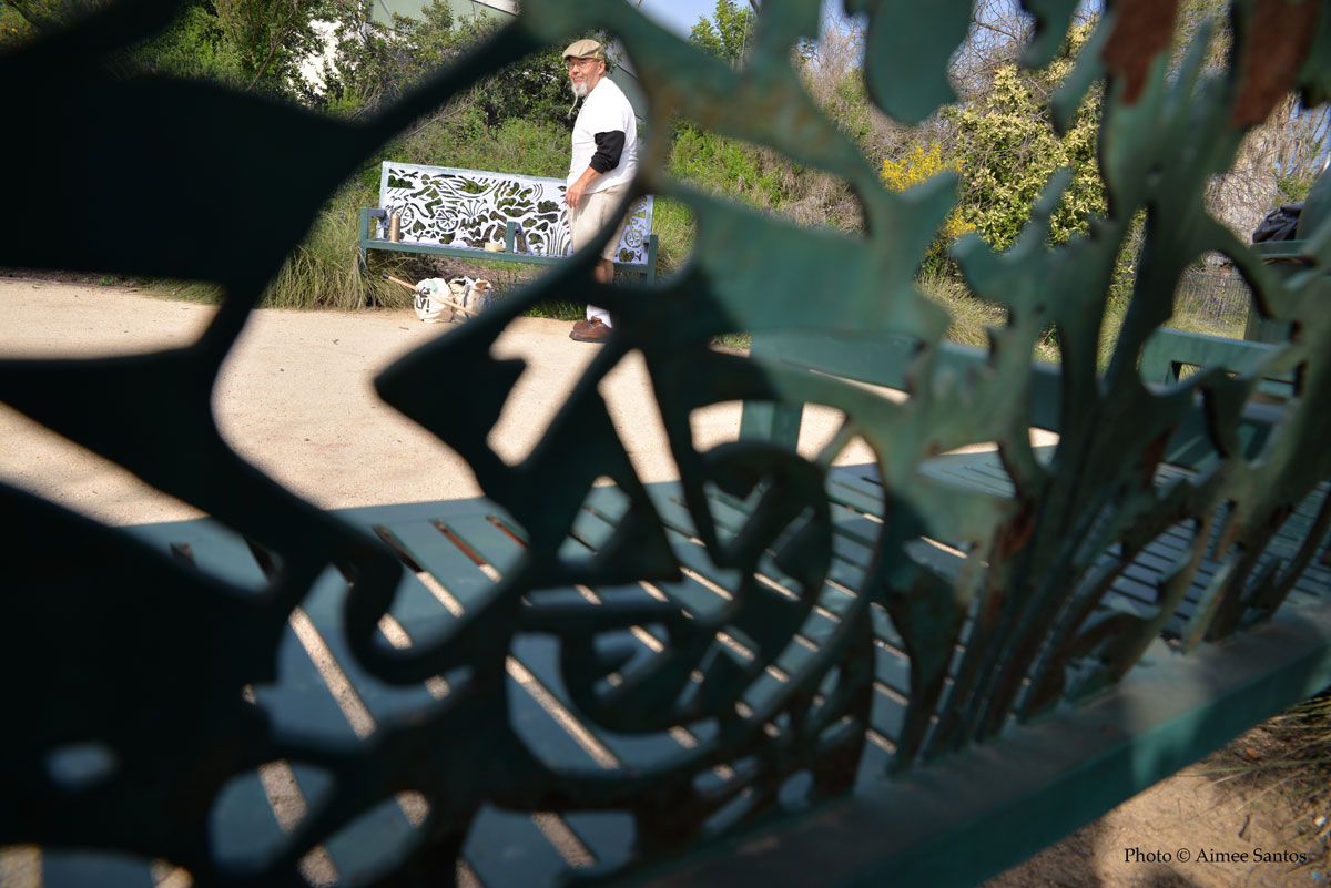 Seen through the art benches at a park near the LA River Limon paints a bench he helped design but felt it could be seen better in a different color so he changed it.