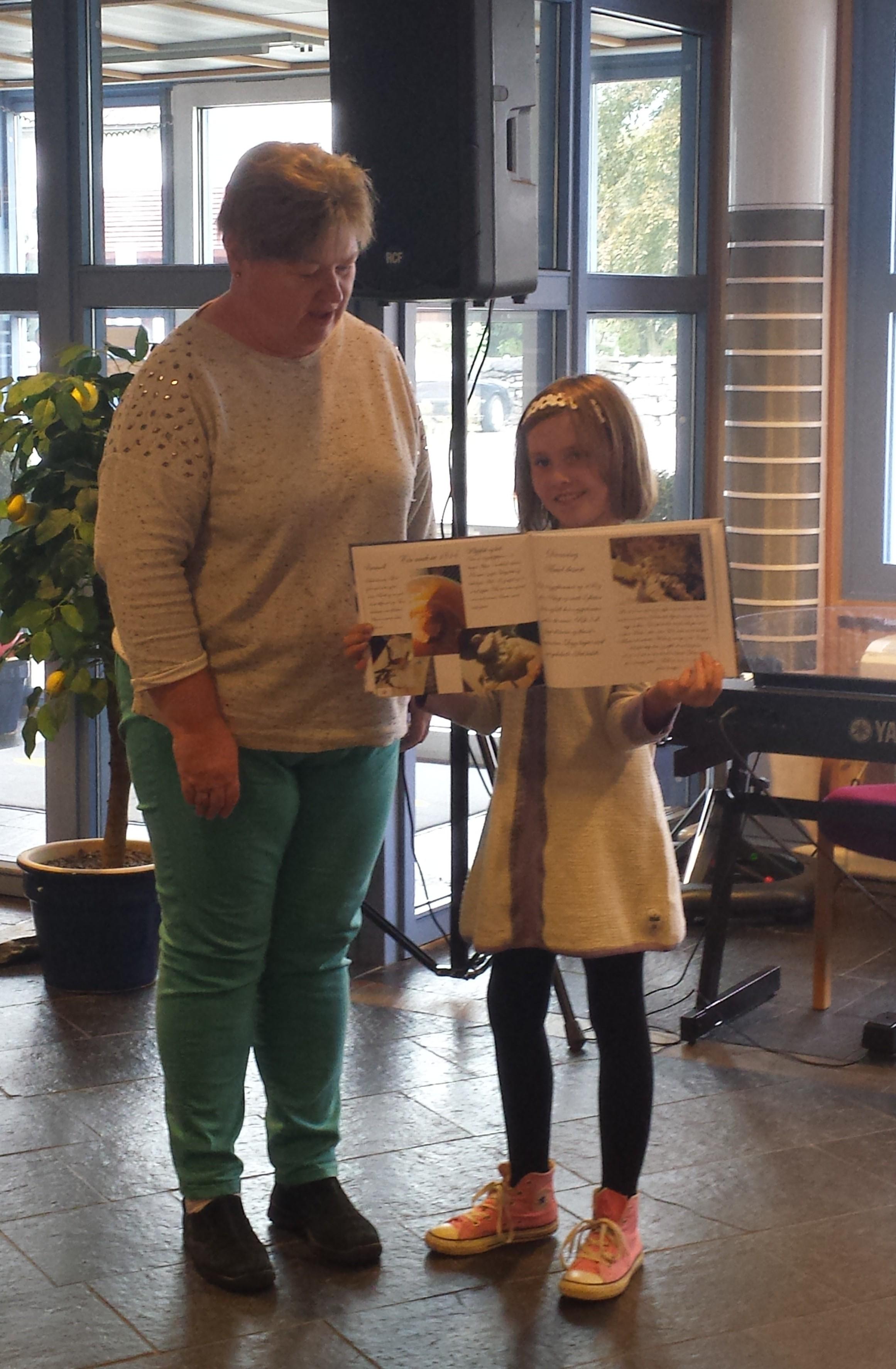 Rektor Astrid og Stina Børressen viser fram boka under programsleppet i Aurland Sparebank