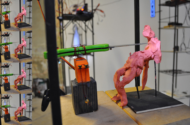 WONDERLUST: Near Violence , 2012 Clay, knife, servo motor, wire, and wood 12 x 8 x 6 inches
