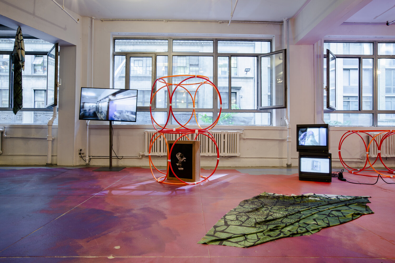 Yona Friedman,  Museum Without Building , Hula hoops and white tape, dimensions vary, 2019.  Nicholas Vargelis,  Prise, Interrupteur, Douille , incandescent bulbs, bent electrical pipe, incandescent colored bulbs, outlet, switches, cable, two video cube monitors, video loops, dimensions vary, 2019.  Dana Levy,  Silent Among Us , video, 5 min. run time each, looped, 2008.  Pradeep Dalal,  Samagri (1-4) , digital chromatic prints on cardboard box supports, 24 x 20 x 6in. each, 2015-2019.  Laetitia Badaut Haussman,  The Silk Prints , 4 Posters, Inkjet on Silk, 55 x 67 in. each, 2019.  Flora Moscovici,  Hula hoop Chack Chack , latex paint on floor, approx. 25 x 40 ft., 2019.
