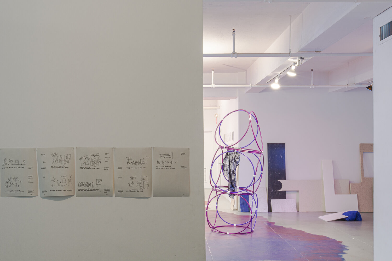 Yona Friedman,  Slideshow (Improvisation in Architect, Build Less, Critical Groupsize, Improvise, Architecture Without Building) , laser print on paper, dimensions vary, 2019.  Yona Friedman,  Museum Without Building , Hula hoops and white tape, dimensions vary, 2019.  Laetitia Badaut Haussman,  The Silk Prints , 4 Posters, Inkjet on Silk, 55 x 67 in. each, 2019.  Theodora Barat,  Natural Acrylic Stones , engineered stones, projected film, approx. 12 x 8 ft, 2019.   Flora Moscovici,  Hula hoop Chack Chack , latex paint on floor, approx. 25 x 40 ft., 2019.