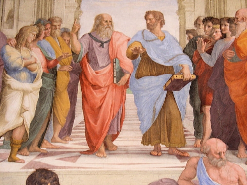 Plato and Aristotle take a walk, as depicted in the famous painting, The School of Athens. The older, otherworldly Plato points up. The younger, earthy Aristotle gestures down. The idealist is barefoot. The realist wears sandals. They both carry books, and are surrounded by many others. Warm sparks, as you might imagine, probably fly.