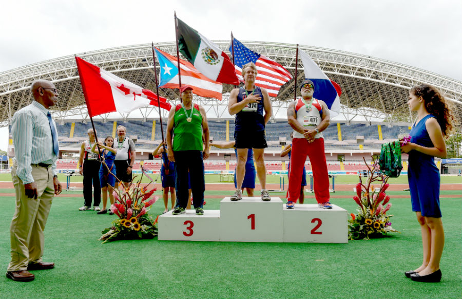 My friend Ed Hearn, during the national anthem, on the awards standwith two strong competitors in Costa Rica.