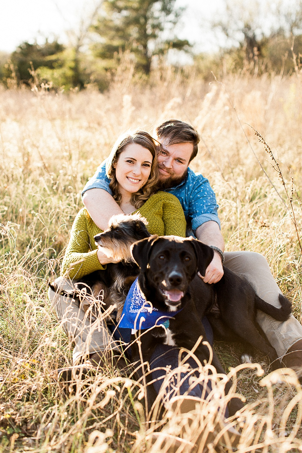 couple snuggles with their dogs in a sunlight grassy meadow