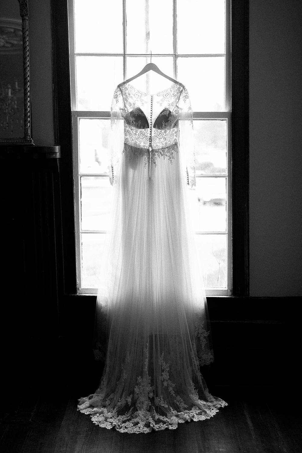 bride's essense of australia gown hangs in a window frame inside the mim's house